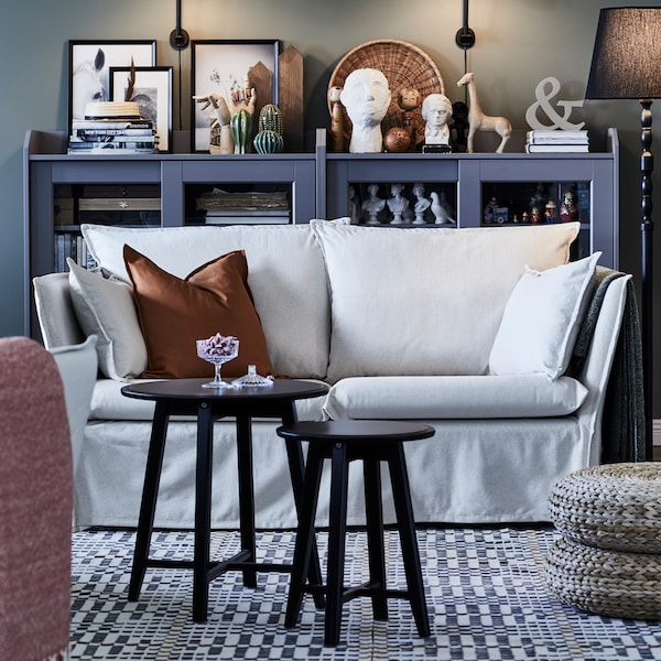 2 round tables in front of a light 2-seat sofa on a patterned rug. A bookshelf with glass doors is behind it.