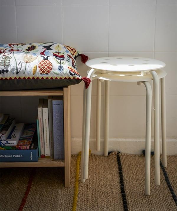 2 stablede, hvide taburetter ved siden af en lav bogreol med en pude på.
