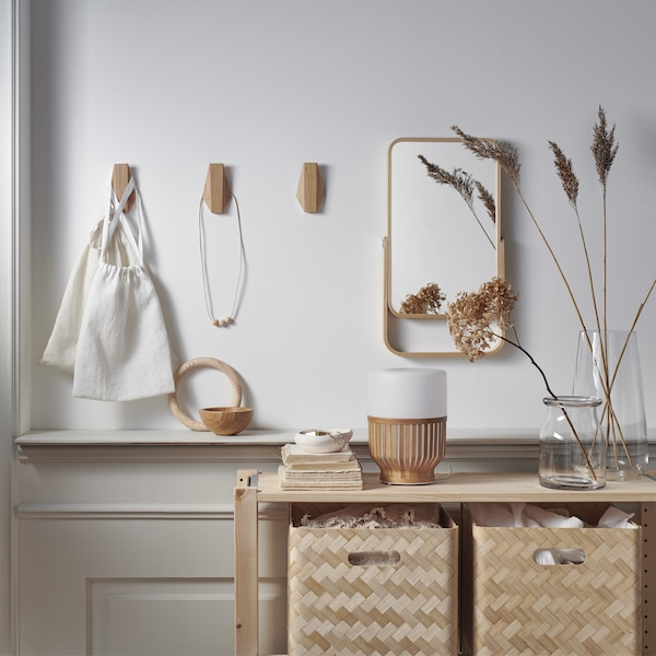 Bamboo storage boxes in a wooden unit, a mirror and wooden hooks on a white wall.