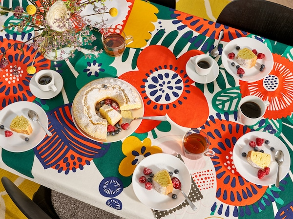 Kitchen with an overview of the kitchen table that has a flower-patterned tablecloth, plates, glasses, mugs and a cake on it.