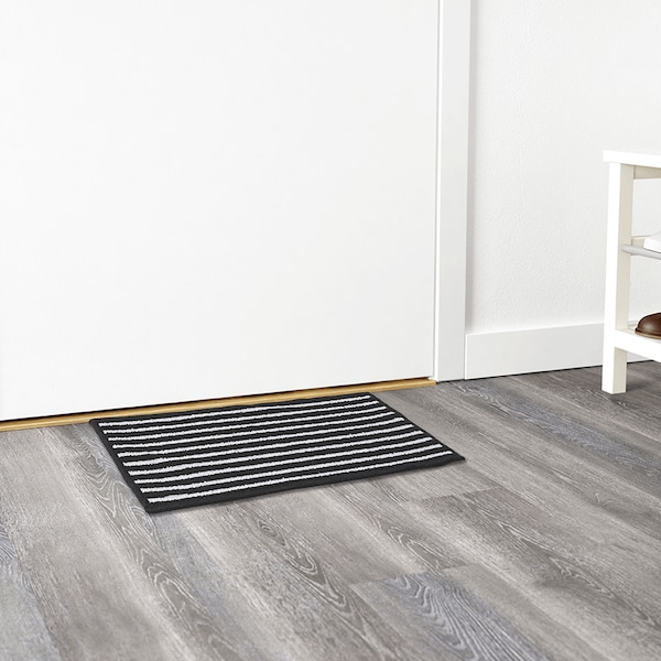 Black and white striped VINSTRUP doormat in front of a white door.