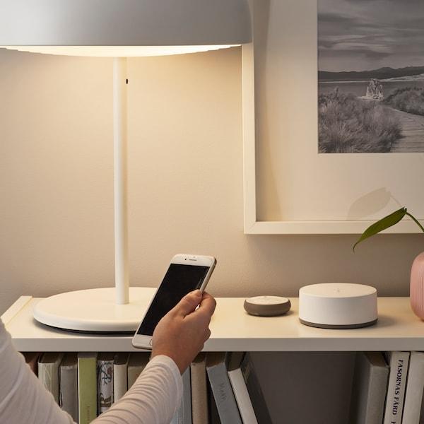 På en låg bokhylla står en bordslampa som styrs via smart belysning med telefonen.