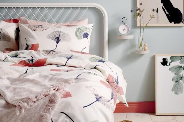 Weiße Bettwäsche mit einem Muster aus blumen in rosa und mintfarben auf einem Bettgestell aus weißem Metall.
