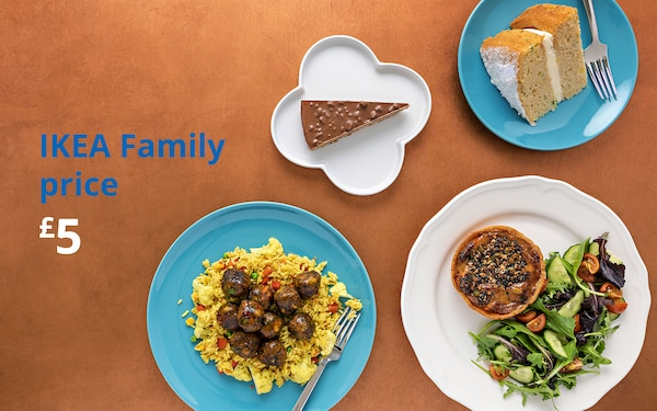 Brown table with a sweet potato tard and salad plate, vegetable biryani plate, almond cake and victoria sponge cake. IKEA Family price £5
