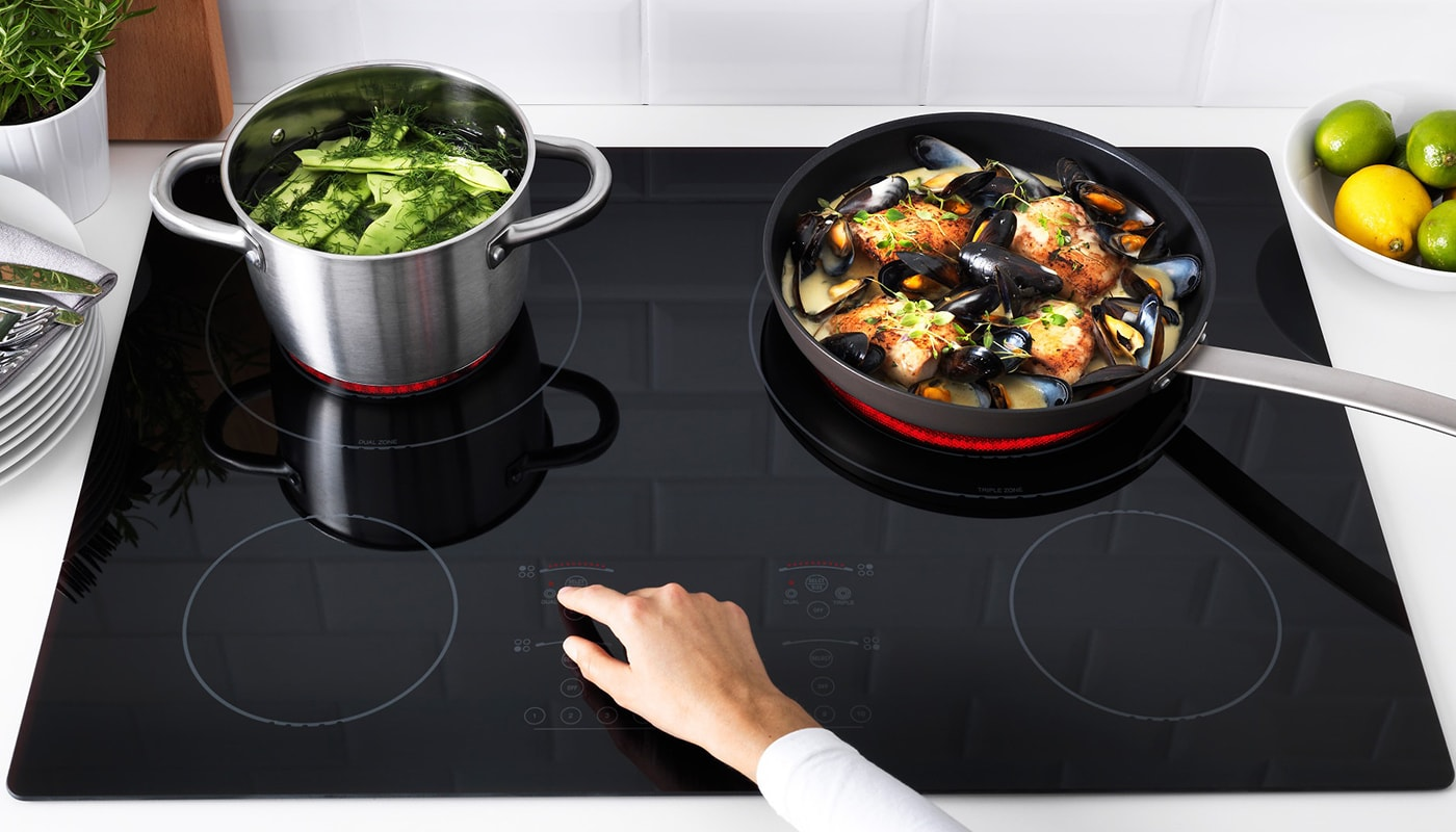 A hand controlling an IKEA NUTID 4 element glass ceramic cooktop