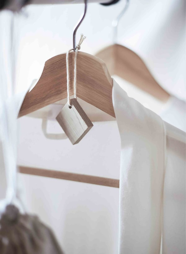 A cedar block sits attached to the hanger of a crisp white shirt.