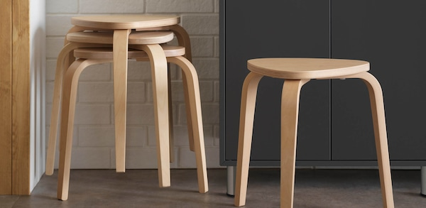 Wooden dining stools stacked in a kitchen setting