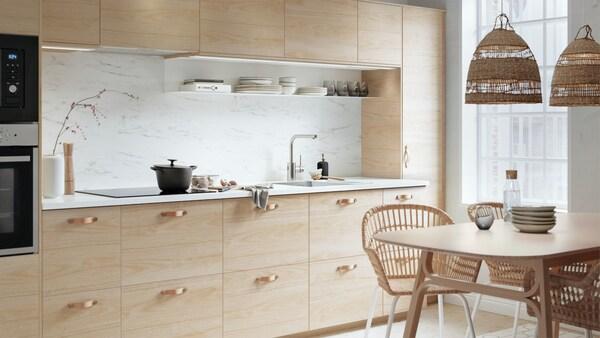 Cuisine légère en bois vierge avec élément naturel en cuir, rotin et roseau.