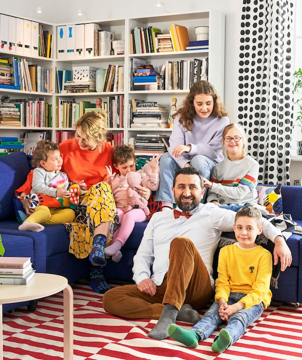 A large family sitting on a blue corner sofa with bookshelves behind them.