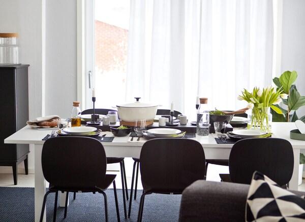 Stol sa stolicama postavljen je za šest ljudi s monokromatskim posuđem i zelenilom.