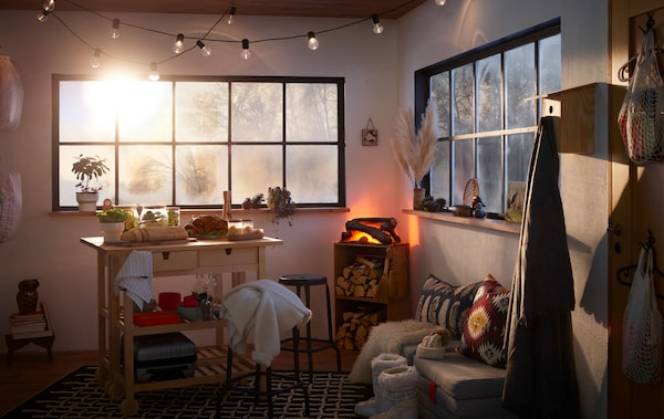 Interior de um pequeno espaço tipo cabana. Pode ver-se a alusão de uma paisagem de inverno pelas janelas, um jantar bufê com peru e a lareira no interior.