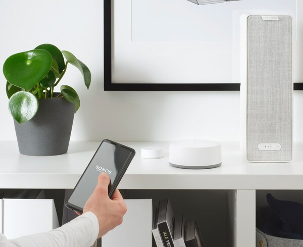 Ein Smarthone mit der SONOS App und einem SYMFONISK Wifi-Speaker in weiß auf einem Regal.