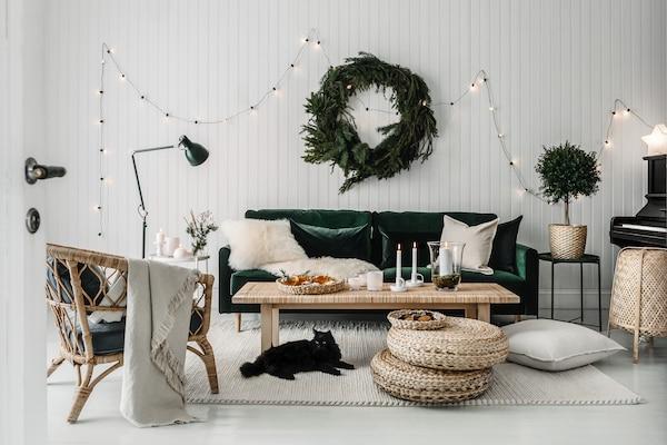Vardagsrum med en grön sammetssoffa och möbler i ljus rotting. Rummet är dekorerat med krans av granris och ljusslinga.
