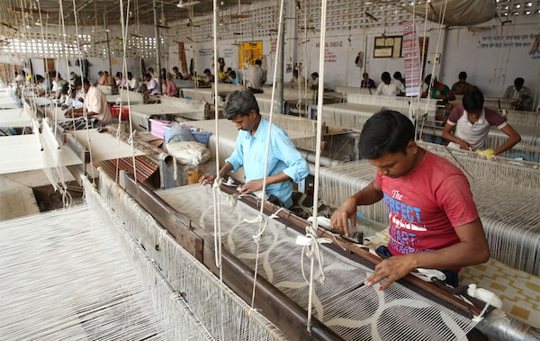 Большой цех, где люди ткут шерсть на станках.