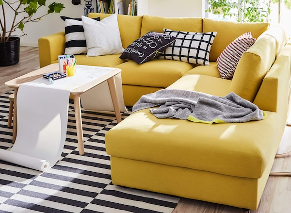 A yellow corner sofa with black and white patterned pillows, a black and white patterned rug and a small coffee table.