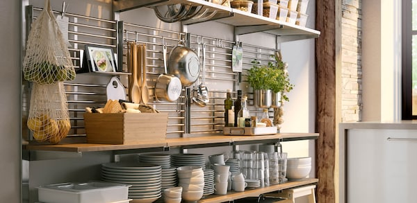 Stainless steel Kitchen storage wall organizers with utensils hanging off railing.