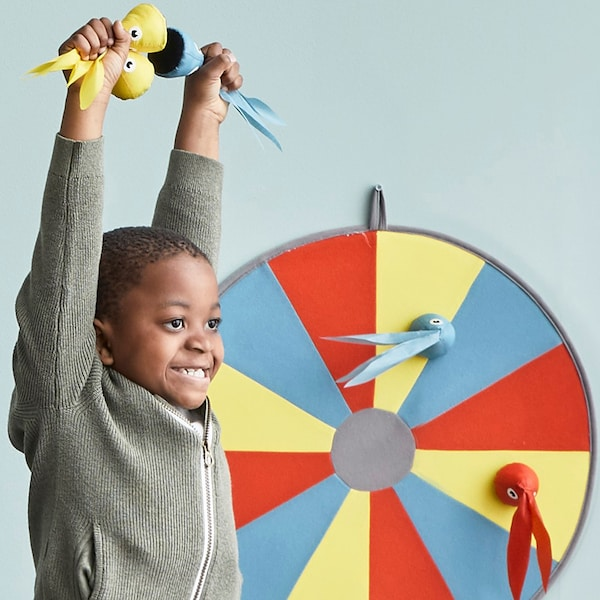 A young boy cheering with his arms up in the air. He is playing a velcro dart board game.