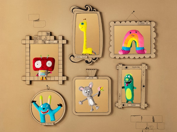 Cardboard frames on a cardboard castle wall, showing pictures of the six SAGOSKATT soft toys.