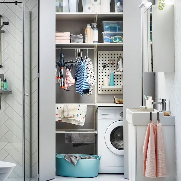 En smart och yteffektiv tvätthörna med tvättpelare och förvaring i ett badrum.