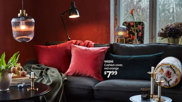 VIGDIS cushion covers on a sofa in a living room decorated for the holidays. Text- VIGDIS Cushion cover, red-orange $7.99
