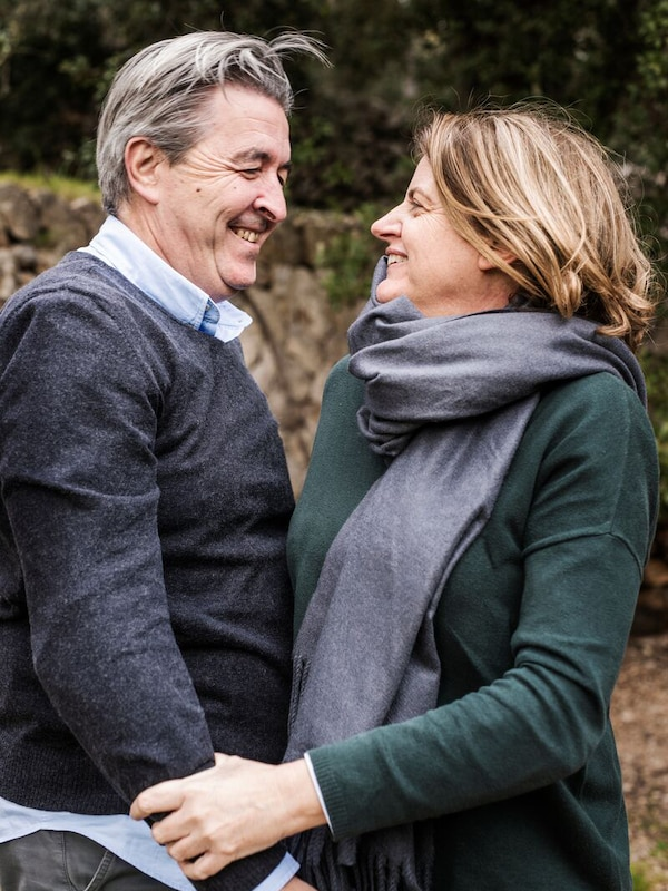 Couple smiling standing in front of trees.