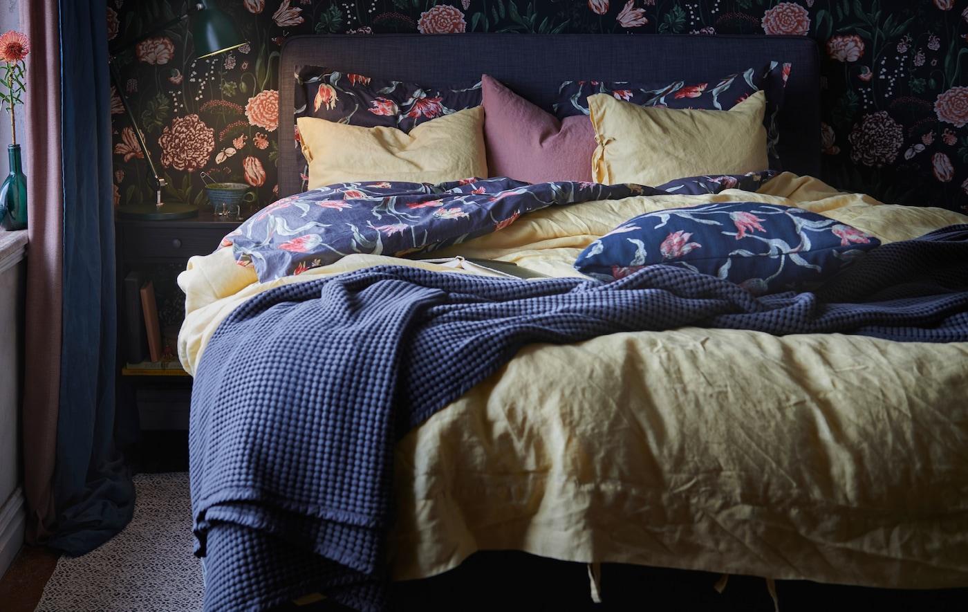 2枚の掛け布団と枕、ベッドカバーが置かれた心地よいベッド。ベッドの隣には、点灯したランプとマグが置かれたベッドサイドテーブル。