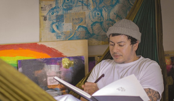 2SLGBTQ+ campaigner, Fox Fisher, is sitting in a hammock, surrounded by pieces of art. He is writing in a sketchbook.