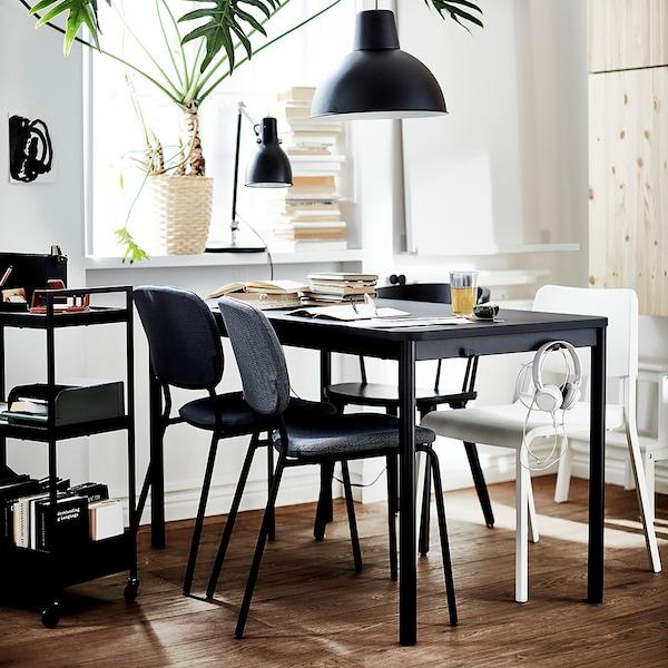 โต๊ะอาหารสีดำ มีเก้าอี้สีดำ 3 ตัวและเก้าอี้สีขาว 1 ตัว