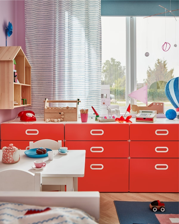 창문 앞에 레드 서랍장 3개가 놓여 있는 아이 방, 서랍장 상판에는 장난감과 놀이용품을 놓을 수 있는 공간이 마련되어 있는 모습