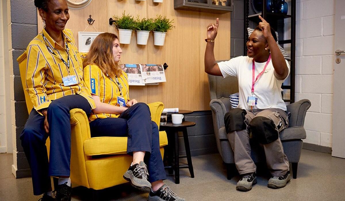 3 IKEA Mitarbeiter unterhalten sich. IKEA legt Wert auf Gemeinsamkeit, Begeisterung und Optimismus.