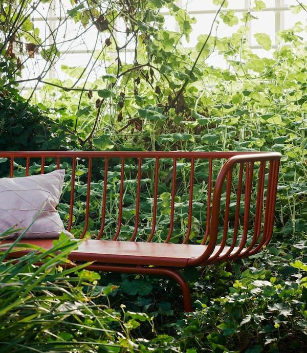 3:n istuttava BRUSEN-sohva kasvihuoneessa. Ympärillä on vehreä maisema.