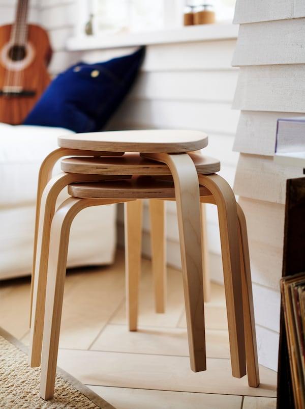 3 stablede KYRRE taburetter ved en hvid, træbeklædt væg. I nærheden står en hvid sofa med en guitar.