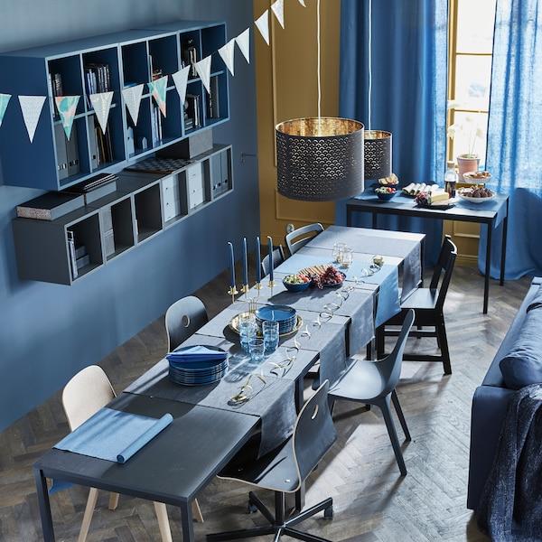 3 TÄRENDÖ Tische in Schwarz sind der Länge nach zusammengeschoben und ergeben so eine lange Tafel für eine Party. Darauf liegt MÄRIT Tischläufer in Dunkelblau. Der vierte Tisch beherbergt das Büfett.