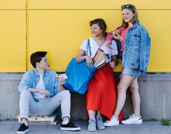 3 unge mennesker står ude foran en gul IKEA butik
