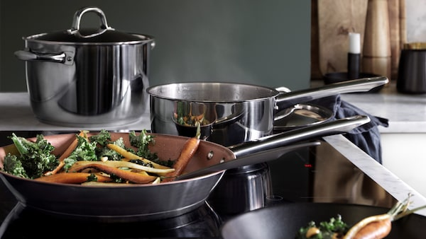 Vegetables cooking in pots and pans on cooktop