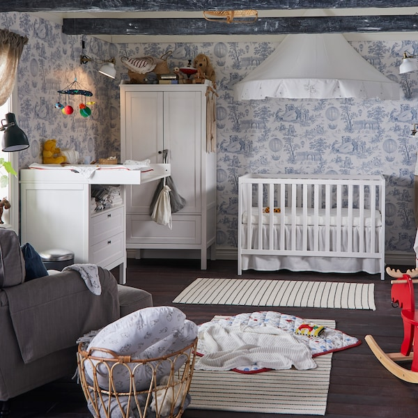 Children's room with blue/white wallpaper, a white cot and changing table, a white wardrobe and two white/black striped rugs.