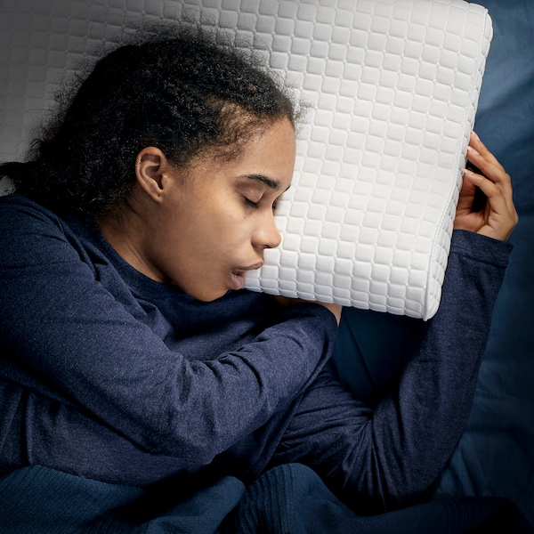 A young girl, laying on her side, is sleeping deeply on IKEA ROSENSKÄRM ergonomic pillow.