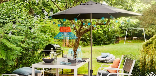 Black umbrella with white and blue outdoor lights hanging from underneath, over an outdoor table and chair set.