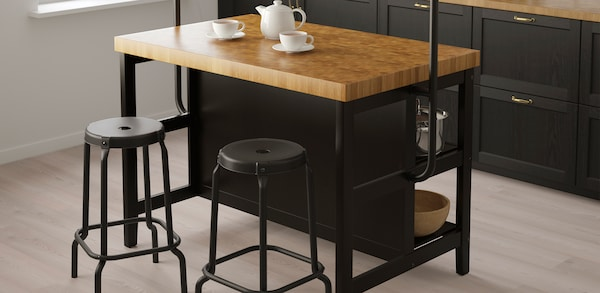 Black kitchen island with wooden top and black barstools.