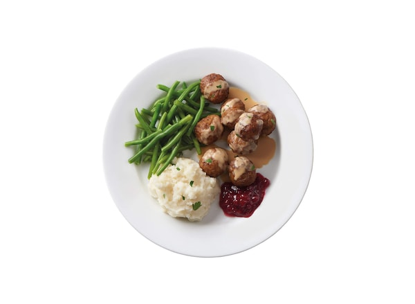 A plate of swedish meatballs with lingonberry sauce, potatoes and green beans against a white background.