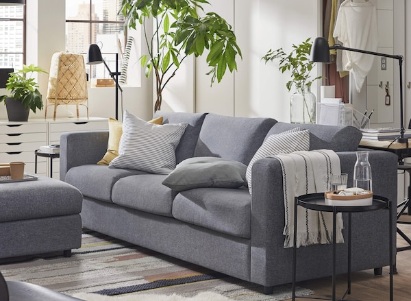 A gray sofa in a living room with a round black side table next to it and potted plants behind it.