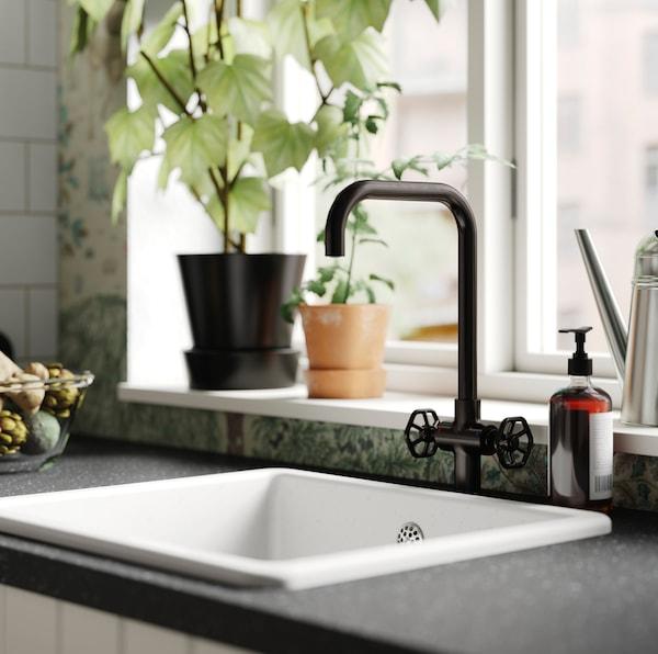 Crna IKEA GAMLESJÖN miješalica za vodu s vretenastim ručicama koje djeluju tradicionalno.