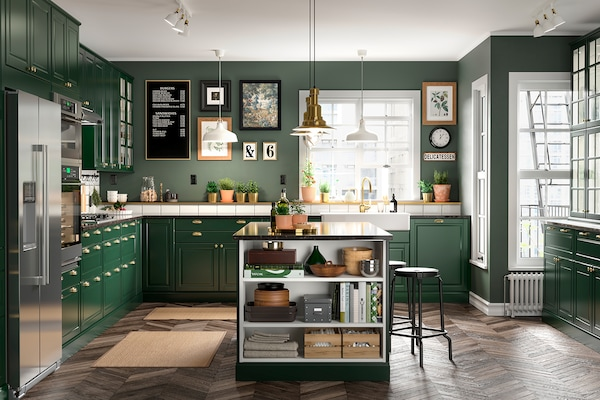 Kitchen with green cabinets and gold accents.