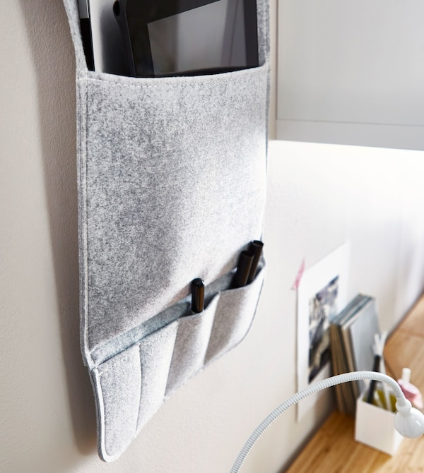 A grey fabric wall organiser hanging on a wall above a desk, with multiple pockets to hold pens and office supplies.