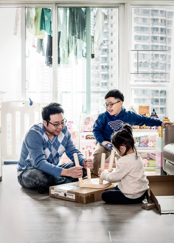 A father playing on the floor with his young children.