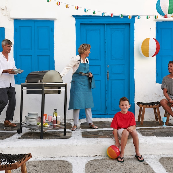 Outdoor scene, with a man and woman standing by a grill with a boy sitting on the floor.