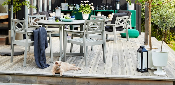 Gray outdoor dining table and chair on a wooden porch