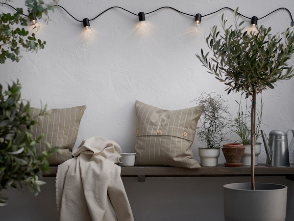 JOFRID throw on a bench, with pillows and various smaller trees and plants in pots.