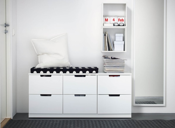 A low drawer unit with six drawers, a white pillow and seating pad on top and a white shelving cabinet wall-mounted above.