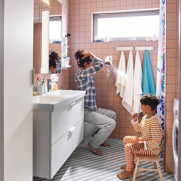 En kvinna och barn i ett rosa badrum som sitter och borstar tänderna.